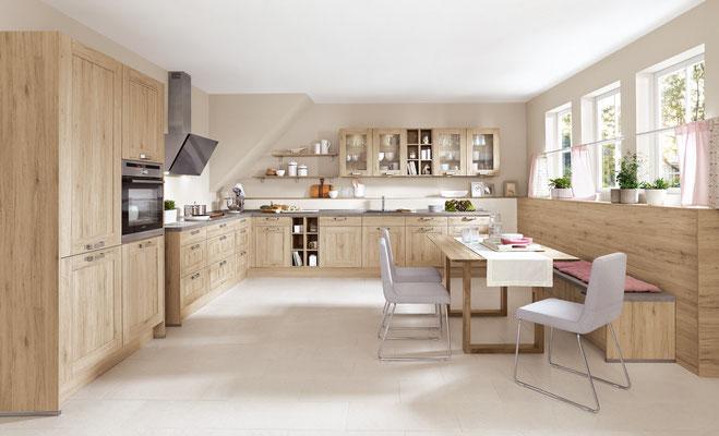 Wohnküche mit holzfurnierten Fronten und ergonomisch verbautem Backofen.
