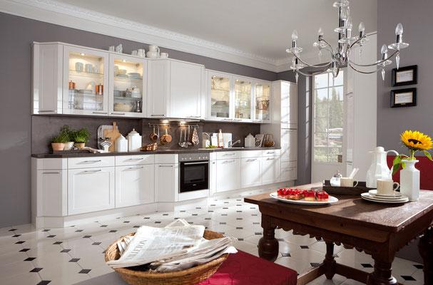 Klassische weiße Küche mit Klasfronten und dunkelbrauner Arbeitsplatte.