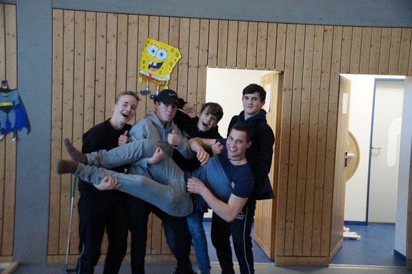 Vier Jungs in der Halle halten einen Mitarbeiter hoch