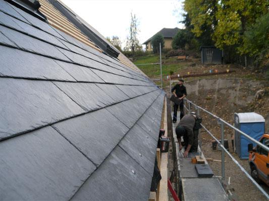 Das Dachdecken mit den Schieferplatten beginnt