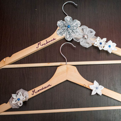 Cintres personnalisés pour les tenues de cérémonie de la mariée et du marié, décorés de fleurs en tissus blanc et argenté par La mariée en fleur