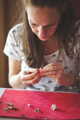Confection artisanale d'une couronne de fleurs en tissus et papiers pour un mariage thème Japon en rose, rouge et blanc par La mariée en fleur