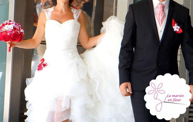 Couple de mariés avec bouquet, personnalisation de robe et boutonnière La mariée en fleur