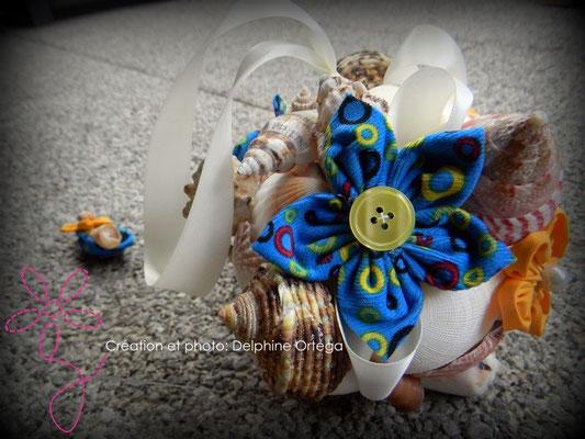 Bouquet de mariée oirginal et éternel en fleurs en tissu et coquillages. Thème Mer pour un mariage à la plage. Gros plan fleur bleue