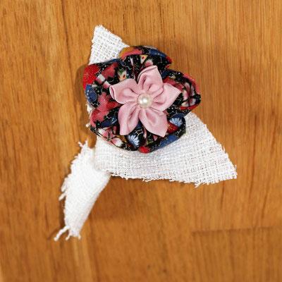 Boutonnière marié coordonnée au bouquet de la mariée avec petite fleur en tissu à motifs imprimés fleuris multicolore, coton blanc et satin rose pale