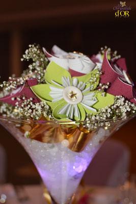 Pierre et Bernard. Centre de table en origami dans vase martini. La mariée en fleur. Framboise, vert et doré