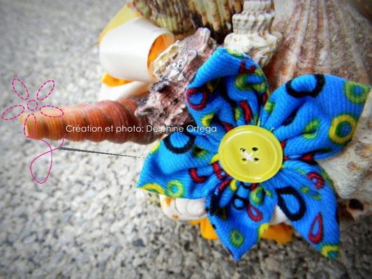 Bouquet de mariée original et éternel en fleurs en tissu et coquillages. Thème Mer pour un mariage à la plage. Gros plan fleur bleue