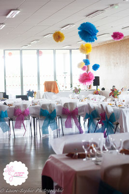 Décoration DIY salle de mariage rose, bleu et jaune. Pompons en papier de soie, housses de chaises avec noeuds colorés et moulins à vent
