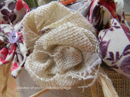 Détail bouquet de mariée original en fleurs éternelles de tissu et papier. Rose en toile de jute
