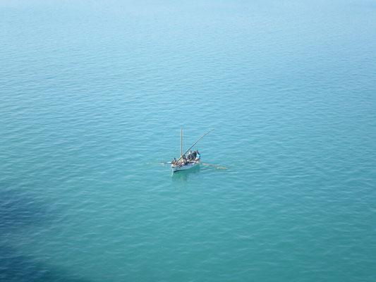 Einige Fischer queren den Kanal und müssen sehen, dass sie den Schiffen ausweichen.