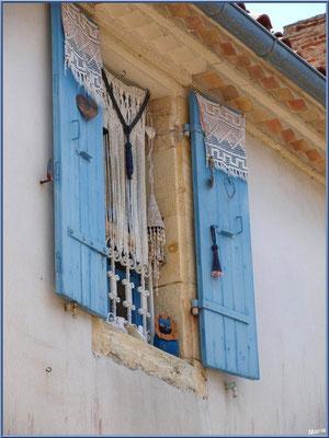 Fenêtre décorée aux volets bleus à Talmont-sur-Gironde (Charente-Maritime)