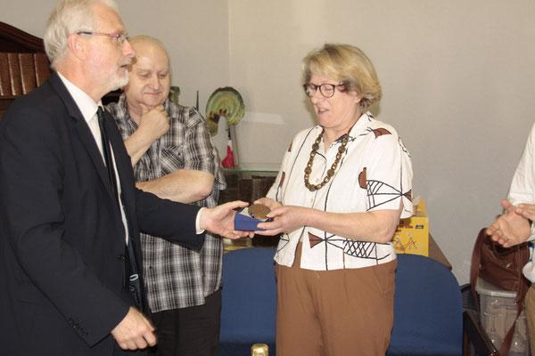 Jean-Jacques Stoter remet la médaille du conseil départemental au couple de commerçant.