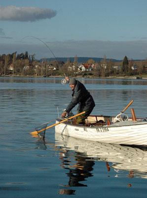 """""""Drüben drillte ein Angler gerade einen Fisch. Die Rute war krumm, und der Mann nahm den Kescher in die Hand."""""""