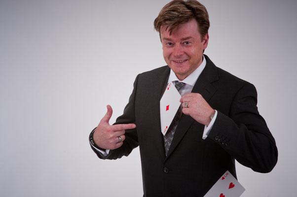 Der Zauberkünstler in Aschaffenburg baut die Spannung auf und hält sie. Er reagiert auf Unerwartetes schnell und witzig. Er legt den Kollegen den Teppich aus.