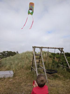 Ole lässt seinen selbstbemalten Drachen fliegen