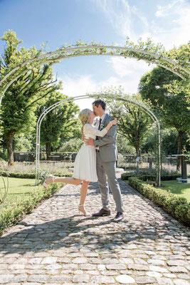 Brautpaar küsst sich im Rosenbogen vom Schlossgarten in Bümpliz