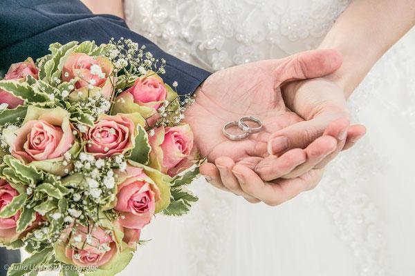 Eheringe in den Händen vom Brautpaar mit Brautstrauss