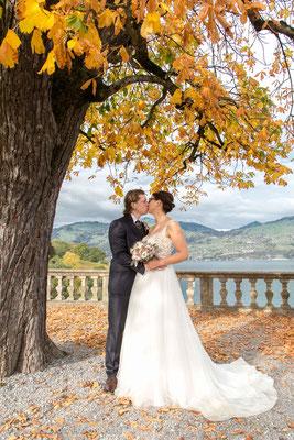 Herbsthochzeit Brautpaar zwischen bunten Blättern und atemberaubendem Ausblick auf den See