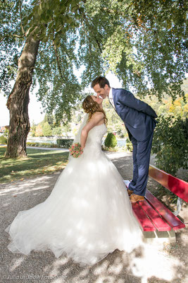 Bräutigam küsst Braut auf einer Bank im Schadaupark, Thun