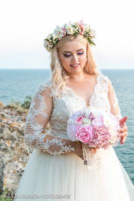 Braut schaut auf Brautstrauss am Schwarzen Meer