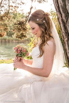 Braut mit Brautstrauss am See