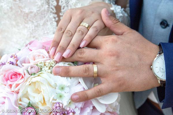 Goldene Eheringe auf einem Brautstrauss