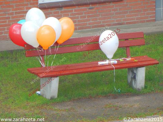 Bunte Luftballons an einer Parkbank