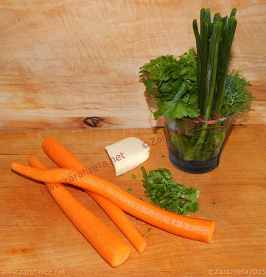 Geschälte Karotten und frische Kräuter