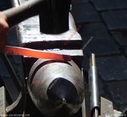 Schmied bei der Arbeit mir glühendem Eisen, Hammer und Amboss
