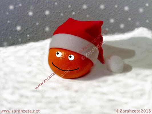 Orange im Schnee mit Weihnachtsmütze