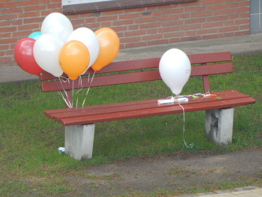 Luftballons an einer Sitzbank