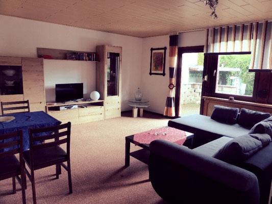 Wohnzimmer mit Esstisch und Schlafcouch