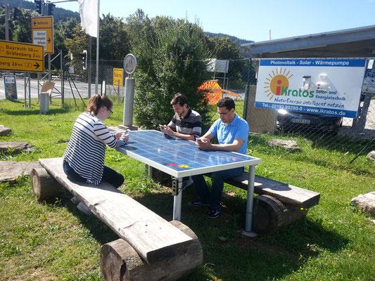 Solartisch vorm Firmengelände der iKratos GmbH mit Aufladefunktion für Wanderer