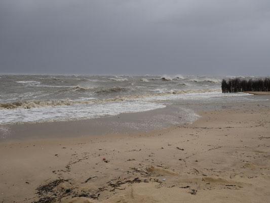 Die Welle gehen schon über den Windschutz am Strand hinaus