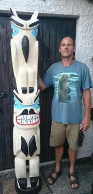 der Künstler mit dem fertigen Pfahl- Motiiv Rabe und Bär