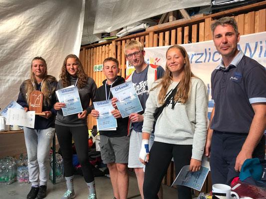 Segler der Bootsklasse Laser Radial erhalten ihre Urkunden von Wettfahrtleiter Marco Martens