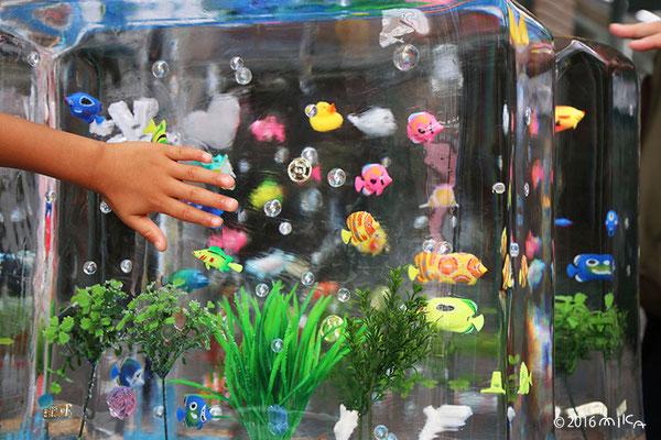 熱帯魚の氷のオブジェをさわって楽しむ人たち(三宮センター街)