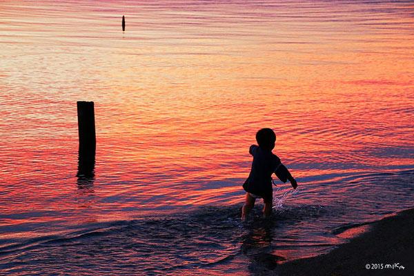 夕焼けの湖を走る男の子