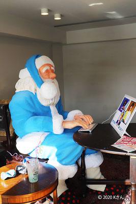 北野通りでパソコンに向かうサンタ