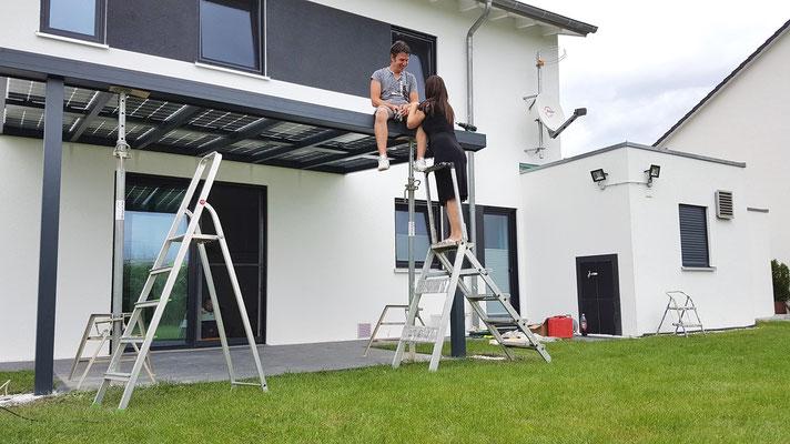 Die Montage von einem Terrassendach lässt sich bequem zu zweit ausführen.