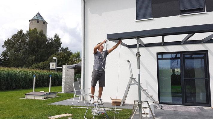 Führen Sie durch die Bohrungen im Dachsparren die Kabel entweder zum Wandanschluss oder zum Pfosten nach unten durch. Die Kabel sollten durch den Pfosten gehen oder aber oben im Wandanschluss versteckt werden.