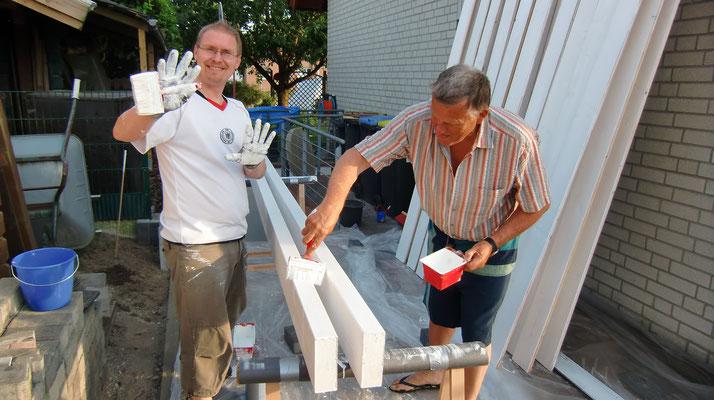 Bauherren streichen das Holz vom neuen Carport
