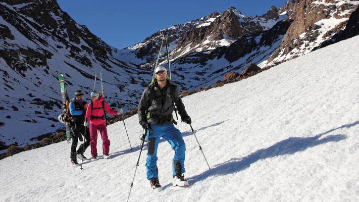 Mit Steigeisen und Ski am Rucksack machen wir uns auf zur letzten Skitour unserer Reise nach Marokko