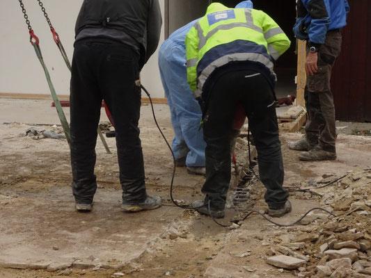 """Drei Arbeiter stemmen und schneiden den Fußboden in """"kleine"""" Stücke."""