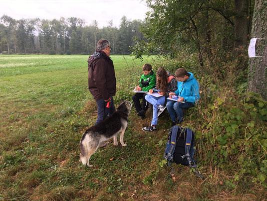 Am Posten 2 wartet KUW-Lehrer Ueli Wagner auf uns. Er erarbeitet mit ihnen den 23. Psalm und ich unterstütze ihn dabei. Er zieht dabei oft Parallelen zwischen dem Psalm und uns Husky`s.