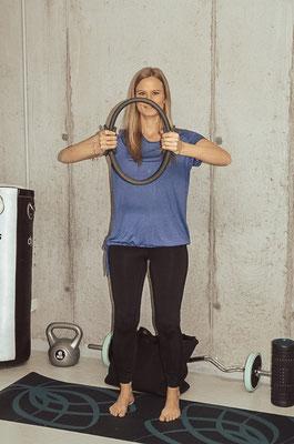 Den Pilatesring vor dem Oberkörper zusammendrücken.  Bauch anspannen, Rücken gerade halten und die Beine leicht beugen (lockerer Stand, nicht durchstrecken).  Kurz halten und dann wieder locker lassen. 15-20 Mal wiederholen