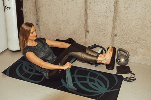 Bauch: Auf die Matte setzen und Oberkörper und Beine anheben. Das Band mit beiden Händen umschließen und in einer fließenden Bewegung das Band von der Oberschenkelrückseite auf die Oberschenkelvoderseite führen. Beine dabei anziehen und strecken.  15 Wie