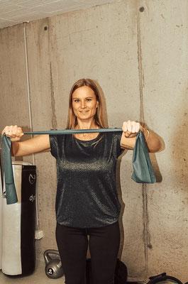 Brust:  Fitnessband vor dem Körper in Schulter/Brust Höhe mit beiden Armen umfassen und auseinanderziehen. Kurz halten und 15-20 Mal wiederholen. Beine leicht gebeugt, Rücken gerade, Bauch angespannt