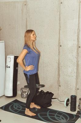 In eine leichte Hocke gehen (Bauch anspannen, Rücken gerade halten) und den Pilatesring zwischen den Oberschenkeln einspannen und zusammendrücken, kurz halten und wieder locker lassen. 15-20 Wiederholungen
