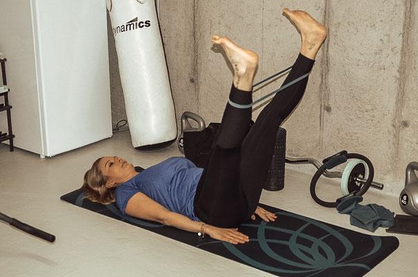 Rückenlage, Beine anheben und Rubberband um die Unterschenken wickeln. Beine öffnen und schließen